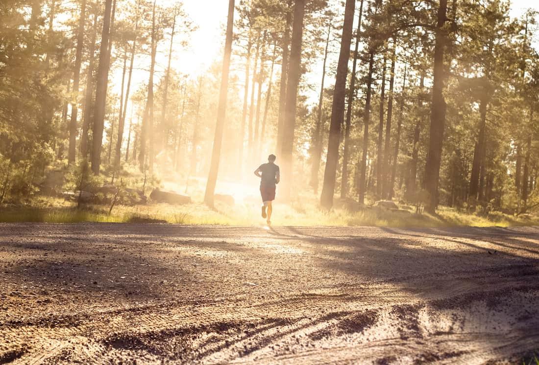 man running through a sunny forest