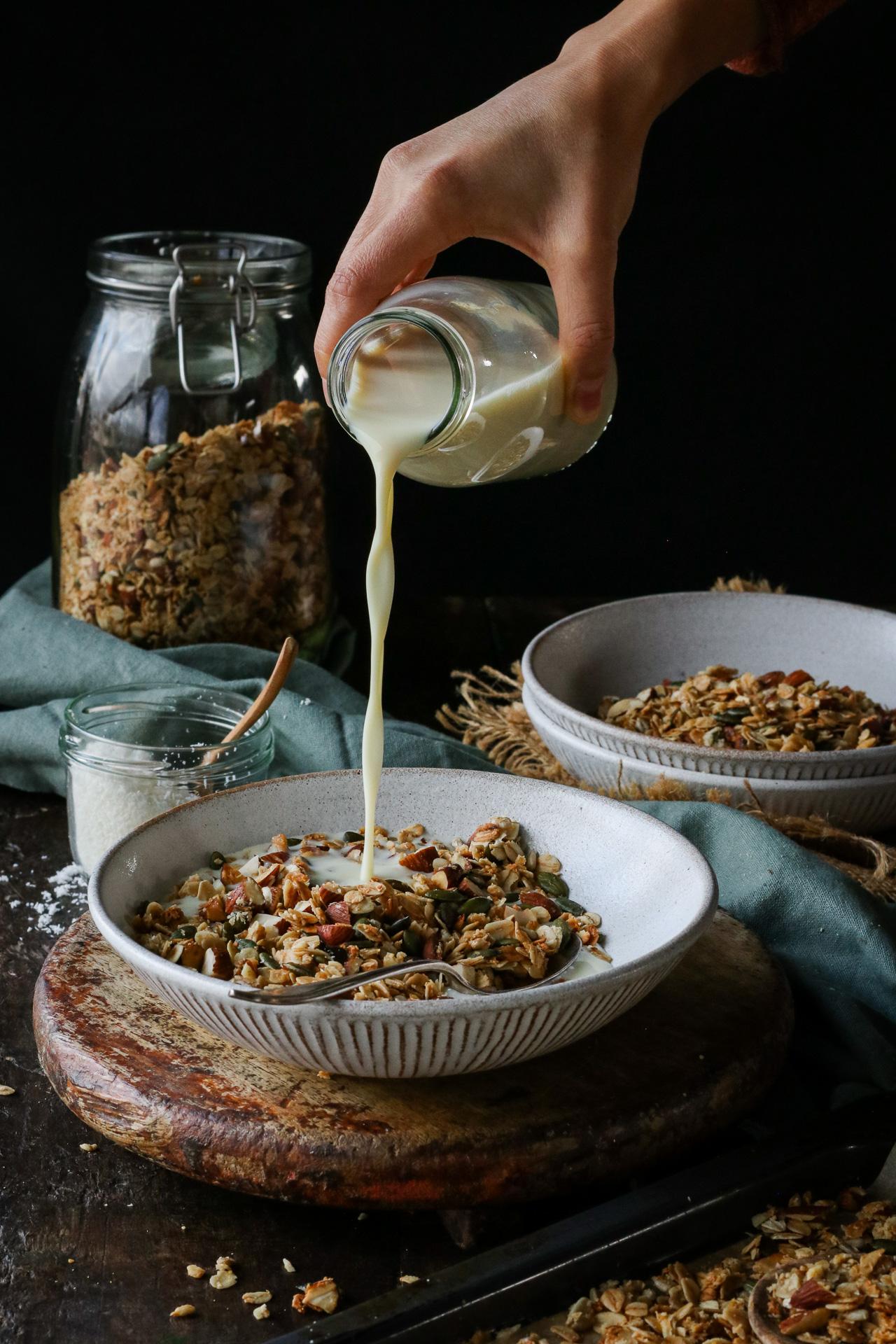 pouring plant-based milk onto granola